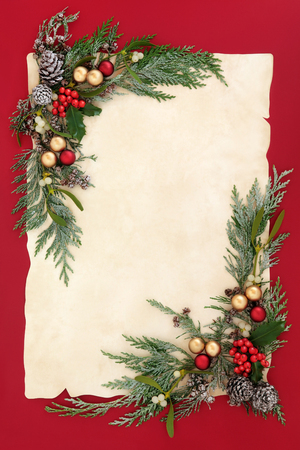 gold christmas decorations: Christmas abstract background border with gold and red bauble decorations, holly, mistletoe, snow covered cedar cypress and pine cones on old parchment paper over red. Stock Photo