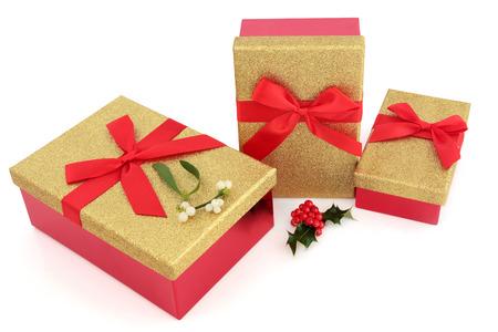 moños de navidad: cajas de regalo purpurina de oro de Navidad con lazos rojos con acebo y el muérdago en el fondo blanco. Foto de archivo