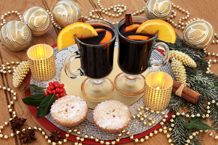 gold christmas decorations: Christmas mince pies and mulled wine, with gold bauble decorations, spices and fruit, candles, holly and snow covered fir over oak background.