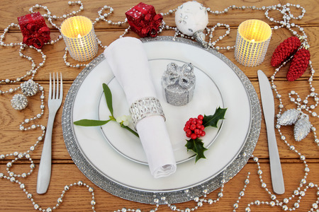serviette: Christmas dinner table setting with white porcelain plates, knife and fork, linen serviette, holly, mistletoe, candles and  bauble decorations over oak background. Foto de archivo
