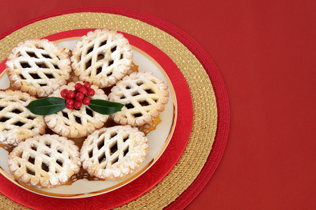 latticed: Christmas latticed mince pie cakes with holly on a red background with copy space.
