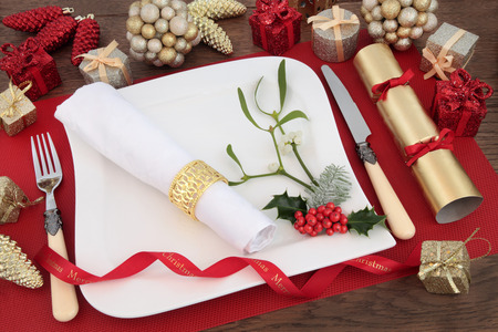 serviette: Christmas dinner table setting with white plate, cutlery, linen serviette, holly, mistletoe, bauble decorations and cracker over on a red place mat on oak background.