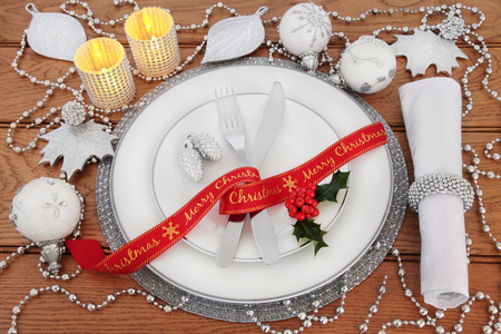 serviette: Christmas dinner table setting with white porcelain plates, bauble decorations, candles, cutlery, linen serviette, red ribbon and holly over oak background. Stock Photo