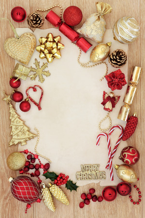 christmas symbol: Red and gold christmas background border with tree decorations and baubles over light oak background on parchment paper.