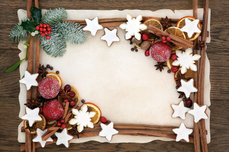 firs: Christmas abstract background border with gingerbread biscuits, cinnamon sticks, spices, dried orange, apple and cranberry fruit with holly, fir and mistletoe on parchment paper over oak wood.