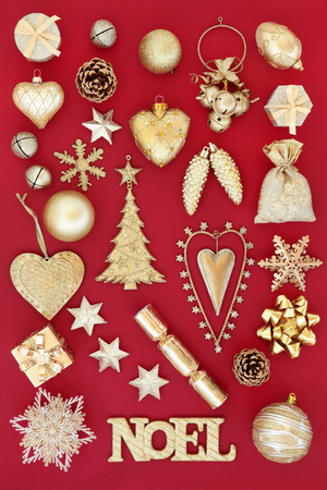 gold christmas decorations: Gold noel sign and christmas tree decorations and baubles over red background.