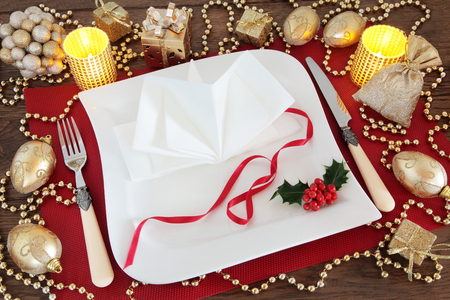 Beautiful christmas dinner table setting with white plates, antique cutlery, napkin, holly, gold bauble decorations and candles on red place mat over oak background.