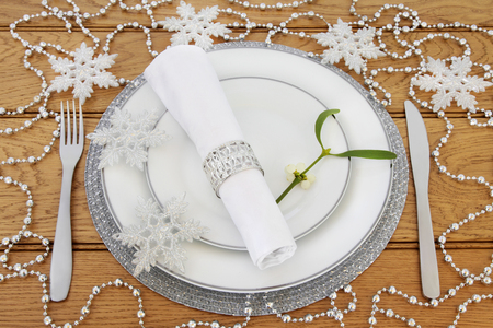 serviette: Christmas dinner table setting with white plates, cutlery, linen serviette with ring, mistletoe, silver snowflake and bead  bauble decorations on oak background.