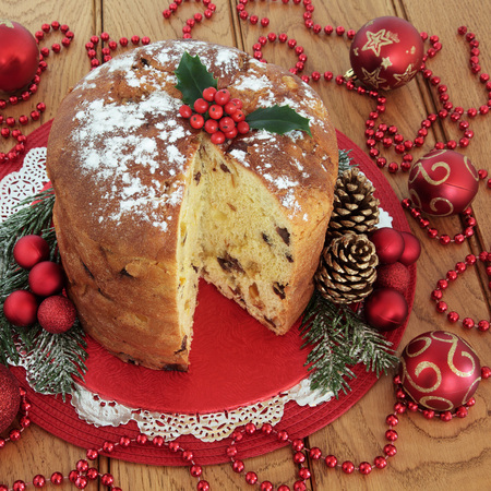 Panettone christmas cake, holly, red bauble decorations with bead strands over oak table background. Stock Photo