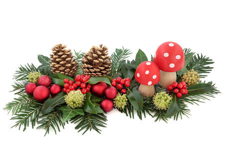 Christmas fantasy decoration with red baubles and fly agaric mushrooms, holly, ivy, gold pine cones and winter greenery over white background.