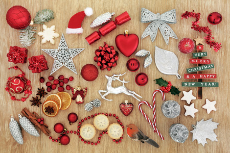 Traditional symbols of christmas with tree decorations, baubles, mince pies, gingerbread biscuits,spices, fruit and  flora over oak wood background. Stock Photo