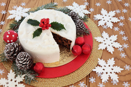 white fly: Christmas food still life with iced fruit cake, holly, snow covered winter greenery, fly agaric decorative mushroom  and white snowflake and red bauble decorations over oak background.
