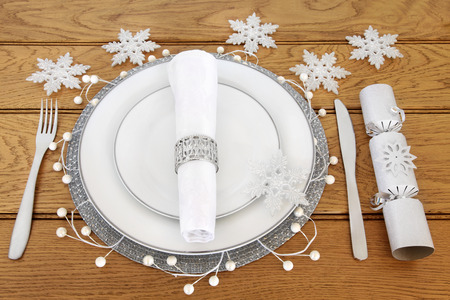 serviette: Christmas dinner table setting with white porcelain plates, cutlery, linen serviette with silver napkin ring, snowflake bauble decorations and cracker over oak background.