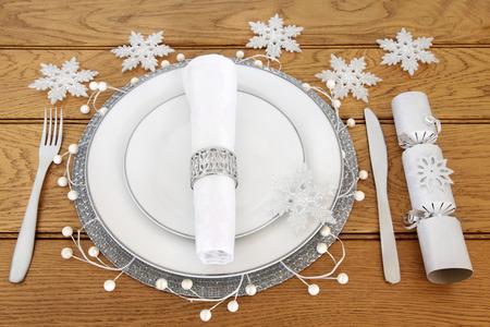 servilleta de papel: mesa de la cena de Navidad y con platos de porcelana blanca, cubiertos, servilleta de lino con el anillo de servilleta de plata, decoraciones de ha de copo de nieve y galleta sobre el fondo de roble. Foto de archivo