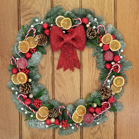 fruit candy: Christmas wreath with red bow decoration, dried fruit, candy canes, baubles, holly, mistletoe, pine cones and snow covered blue spruce fir over oak wood front door background. Stock Photo