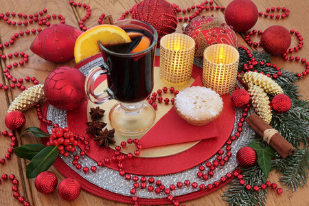 gold christmas decorations: Christmas  mulled wine, mince pie, red and gold bauble decorations, candles, fruit and spices, holly and snow covered winter greenery on oak background. Stock Photo