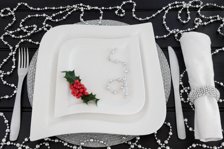 napkin ring: Christmas dinner table setting with white porcelain plates, holly, silver bead decorations, cutlery and linen napkin with ring over dark wood background.