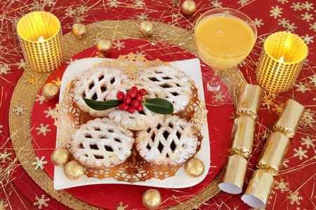gold christmas decorations: Christmas mince pie cakes with egg nog, gold foil wrapped chocolate balls, candles, crackers, holly and snowflake decorations on red background. Stock Photo