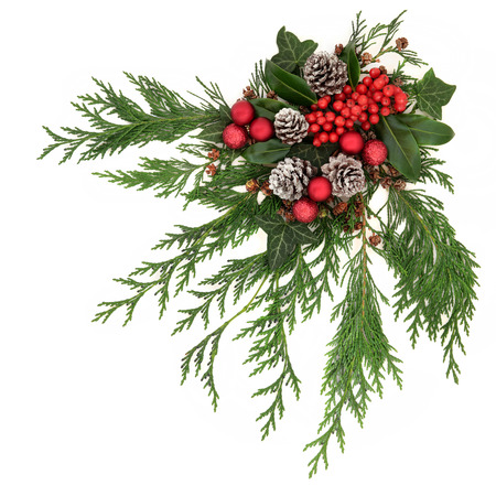 Christmas festive decoration with red baubles, holly with red berries , snow covered pine cones and winter greenery over white background.