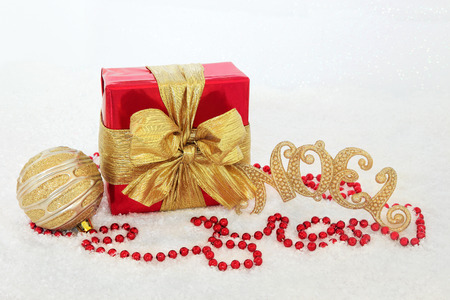 gold christmas decorations: Christmas gift box with gold bow, noel sign, bauble and red bead decorations on snow background. Stock Photo