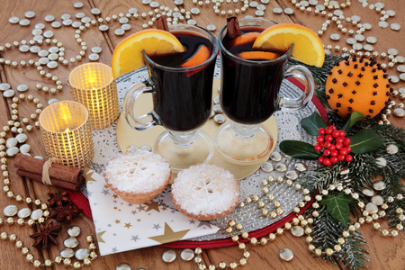 gold christmas decorations: Christmas party food and drink with mulled wine, mince pies, orange pomander, spices, candles, gold bauble decorations,  holly and snow covered fir over oak background.