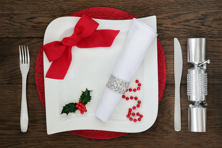 napkin ring: Modern christmas dinner table setting with white square porcelain plate, red ribbon bow, holly, napkin and silver ring, cutlery and cracker over oak wood background.