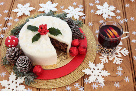 white fly: Christmas cake with holly, mulled wine, snow covered winter greenery with fly agaric decorative mushroom, white snowflake and red bauble decorations over oak background.