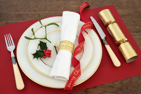 servilleta de papel: Christmas dinner table setting with white porcelain plates, knife and fork, linen serviette, red ribbon, holly, mistletoe and cracker over oak background.