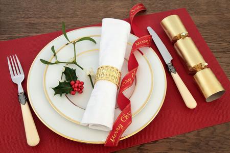 servilleta de papel: mesa de la cena de Navidad en blanco con placas de porcelana, tenedor, cuchillo y servilleta de lino, cinta, el acebo, el muérdago y la galleta sobre el fondo de roble.