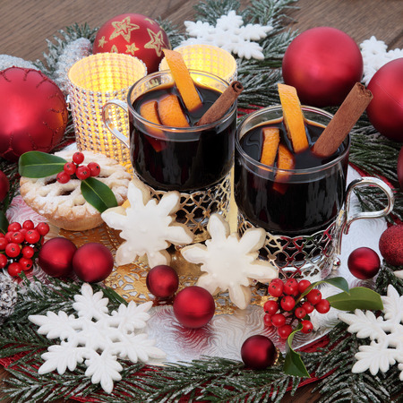snowflake snow: Christmas mulled wine, snowflake gingerbread biscuits, red bauble and white snowflake decorations, candles, orange fruit, holly and snow covered fir over oak background.