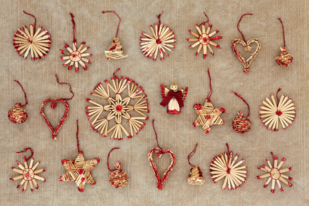old paper background: Straw christmas tree decorations over old grunge brown paper background. Stock Photo
