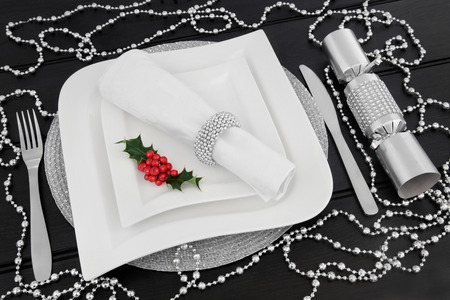 napkin ring: Christmas dinner table setting with white porcelain plates, holly, cutlery, linen napkin with ring  and silver bead decorations over dark wood background.
