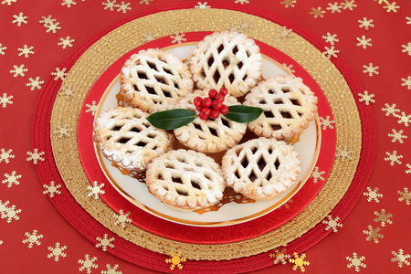 latticed: Christmas latticed mince pie cakes with holly and berries on red background with gold snowflakes.
