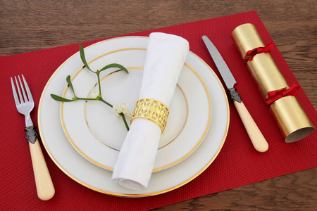servilleta de papel: Christmas dinner table setting with white porcelain plates, antique cutlery, linen serviette and ring, mistletoe and cracker on red place mat over oak background.