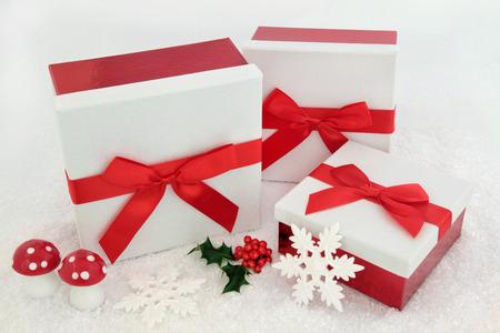 moños de navidad: cajas de regalo brillo blanco de Navidad con arcos de color rojo, el acebo y decoraciones de ha en el fondo de la nieve. Foto de archivo