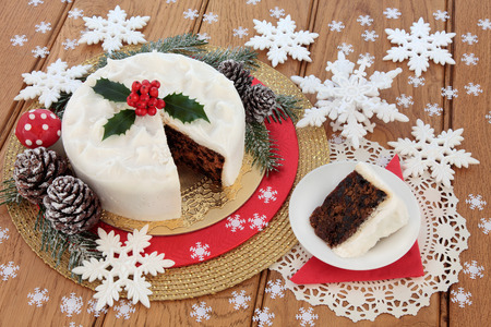 'fly agaric': Traditional christmas cake and slice with holly, snow covered winter greenery with fly agaric mushroom bauble and pine cones with white snowflake decorations over oak background.