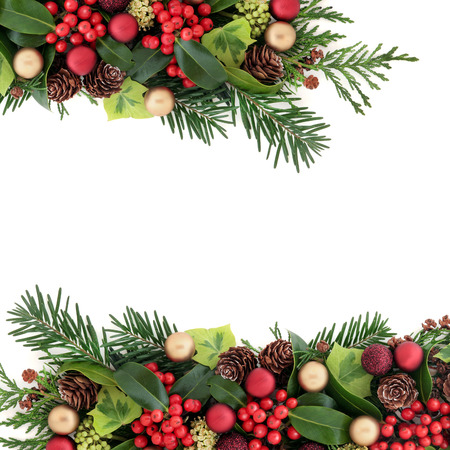 gold christmas decorations: Christmas abstract background border with red and gold bauble decorations, holly with berries, ivy, pine cones, cedar cypress and fir leaf sprigs over white with copy space. Stock Photo