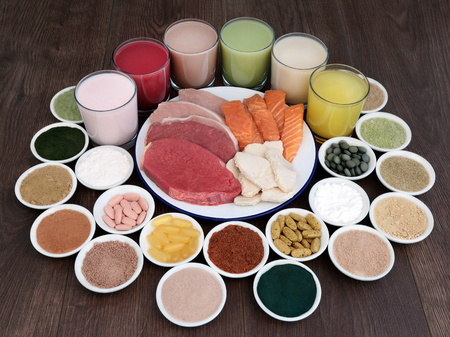 Super food and drinks for body builders with lean meat of steak, chicken and pork with salmon,  dietary supplement powders and vitamin pills on oak background.