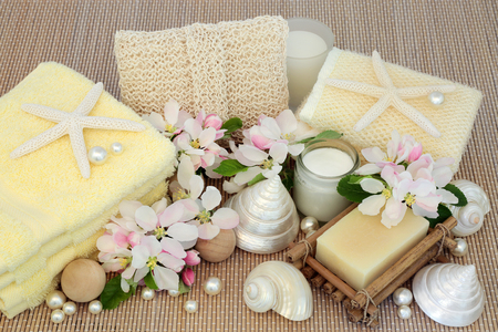 toweling: Fresh spa beauty treatment cleansing products with spring apple blossom, mother of pearl shells and starfish on bamboo background.