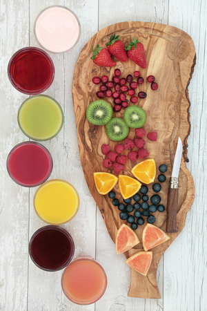 paleolithic: Fresh fruit on an olive wood board with corresponding health smoothie and juice drinks. Strawberry, cranberry, kiwi, raspberry, orange, blueberry and grapefruit, top to bottom.