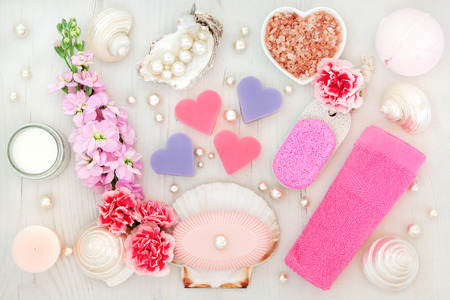 beauty products: Bathroom and spa treatment with flowers, himalayan salt, moisturising cream, pumice, soaps, pink face towel, shells and pearls on distressed wood background.