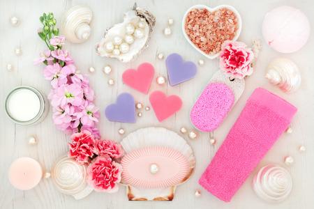 productos de belleza: Cuarto de baño y tratamiento de spa con flores, sal del Himalaya, crema hidratante, piedra pómez, jabones, toallas cara rosada, conchas y perlas en el fondo de madera en dificultades. Foto de archivo