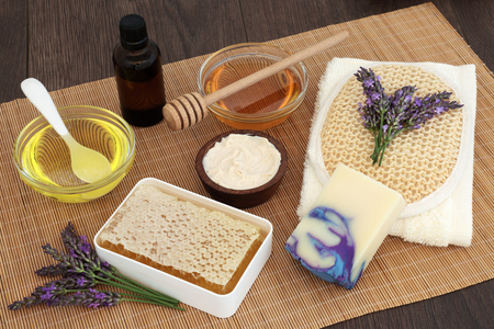 toweling: Lavender flower skin care with honey, almond oil, moisturising cream, soap, essential oil, exfoliating scrub and flannel on bamboo over oak background.