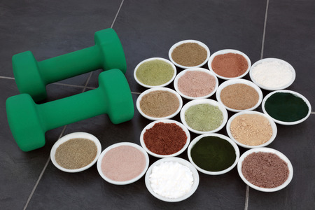 Body building supplement powder and dumbbell weights in porcelain bowls over slate background. Stock Photo