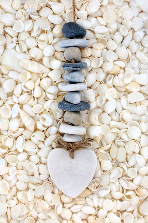 Heart and pebble mobile on white seashell abstract background.