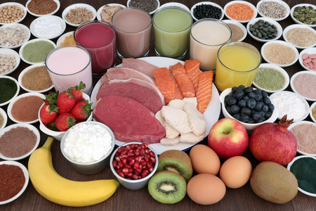 Body building  food and drinks with high protein lean meat and salmon, supplement powders, fruit, nuts, seeds, grains, cereals, pulses, herbs, dairy over oak background. Stock Photo
