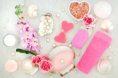 Spa and body scrub cleansing beauty products with flowers, himalayan salt, moisturising cream, soaps, pumice, flannel, bath bomb, pearls and shells. Stock Photo