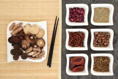 herb medicine: Chinese alternative herbal medicine selection with herb selection in china dishes on a bamboo mat with chopsticks and on marble background.