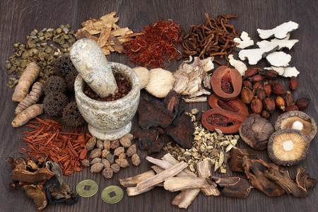 traditional remedy: Traditional chinese herbal medicine selection with mortar and pestle on oak background.
