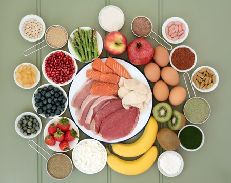 Super food for body builders with meat, fish, fruit, dairy, dietary supplement powders and vitamin pills on green wood background.